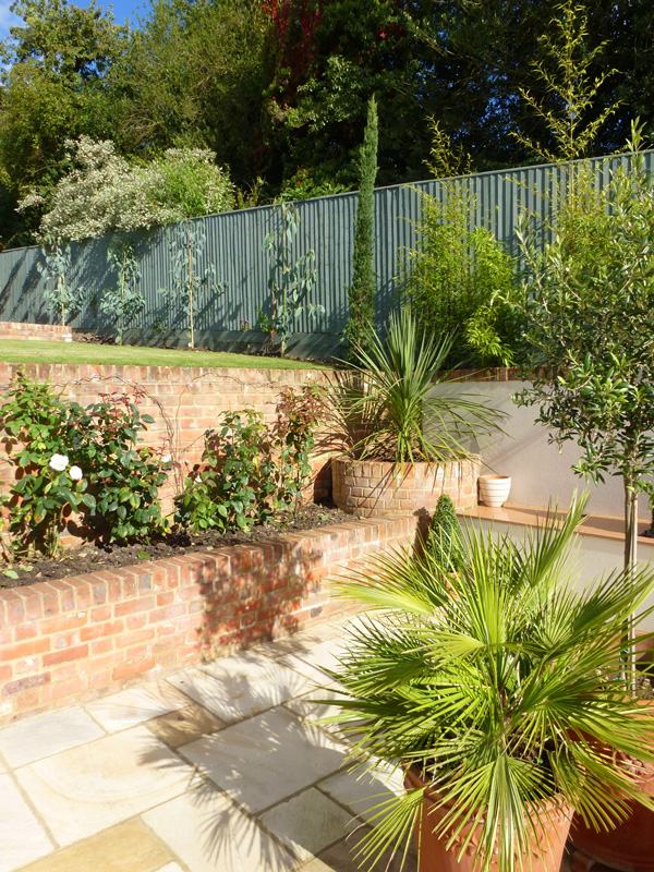 courtyard garden design with red brick retaining walls and flower beds