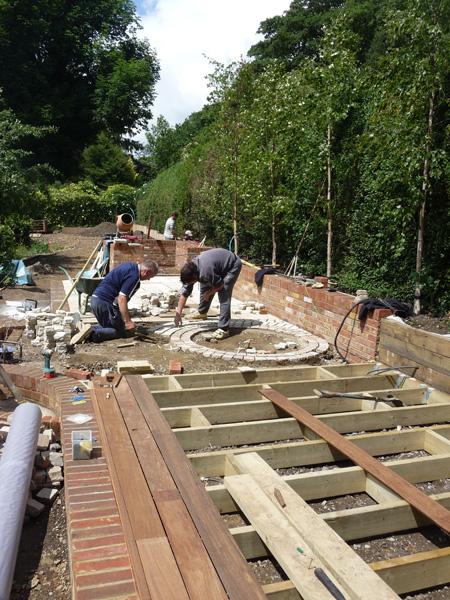 contemporary wooden decking and circular paving in country garden