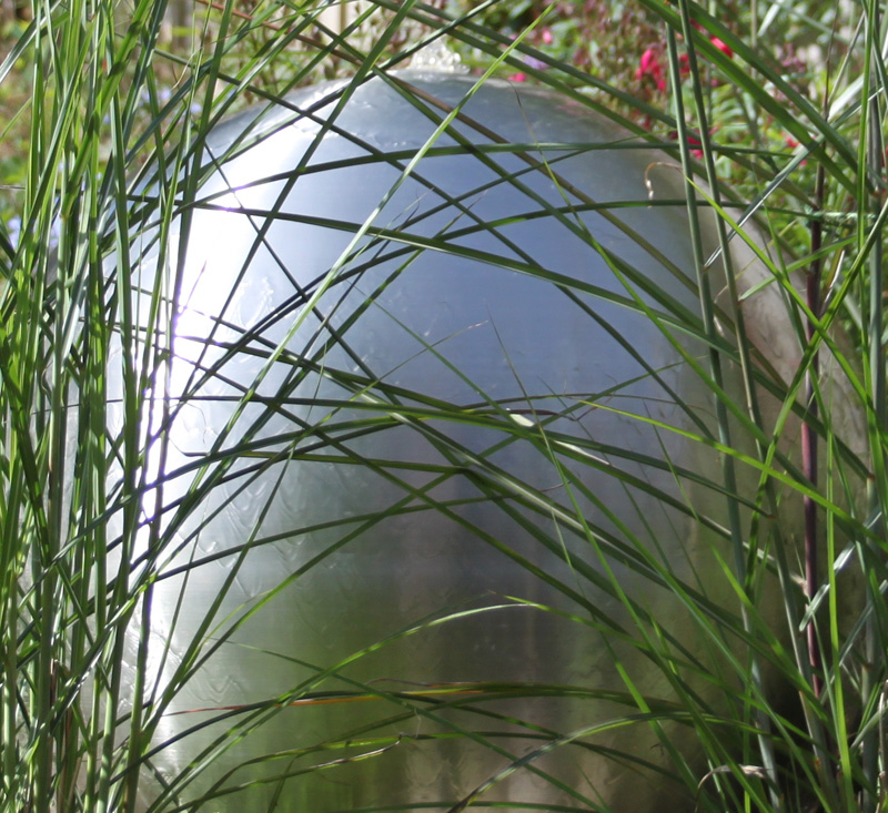 contemporary water feature, spherical steel sculpture in family garden